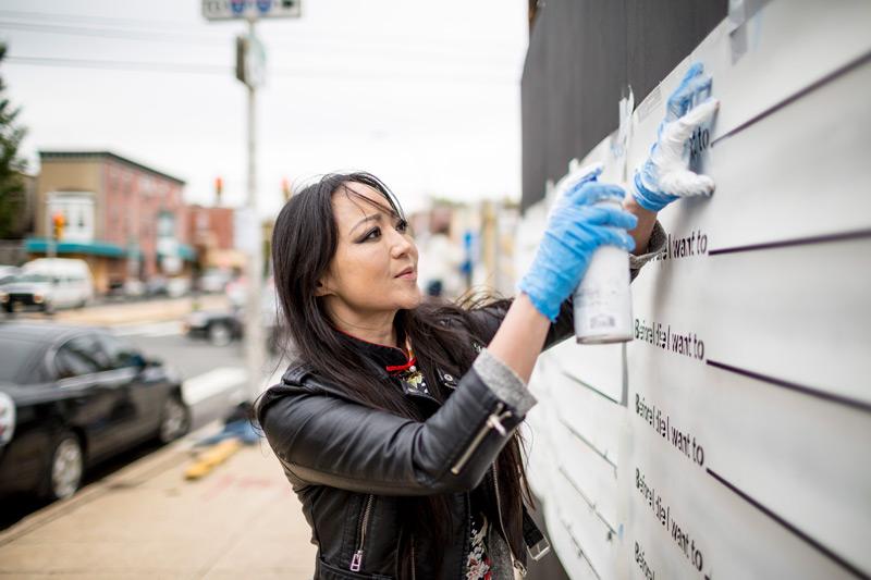 Candy Chang che realizza un muro di Before I Die